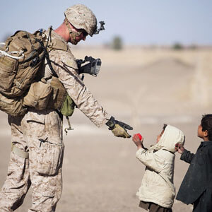 Small children giving a military man an apple